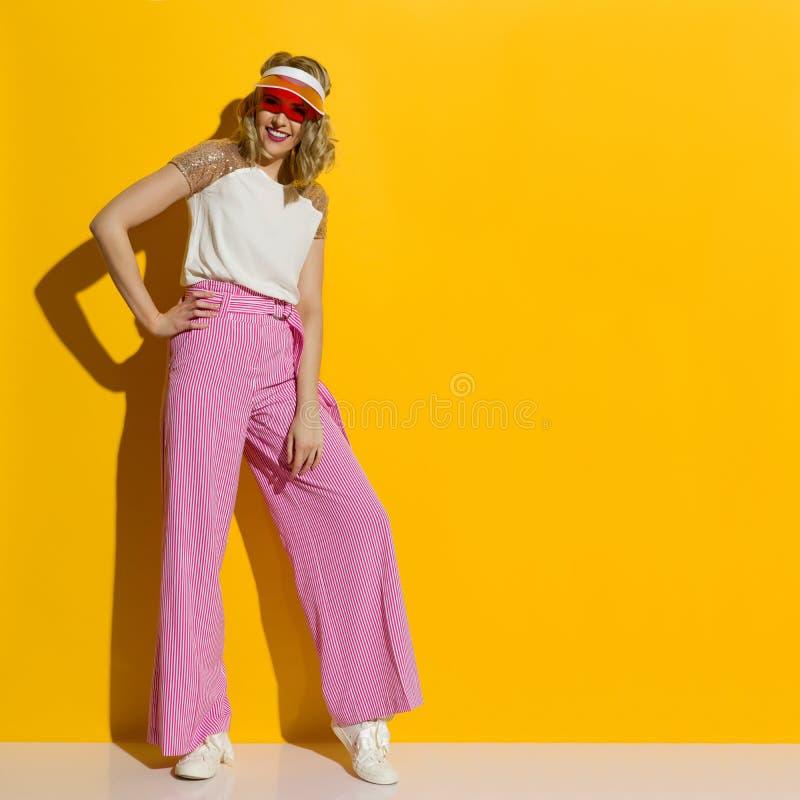 在镶边宽腿长裤和透明遮阳帘的微笑的时装模特儿在阳光下站立 库存照片