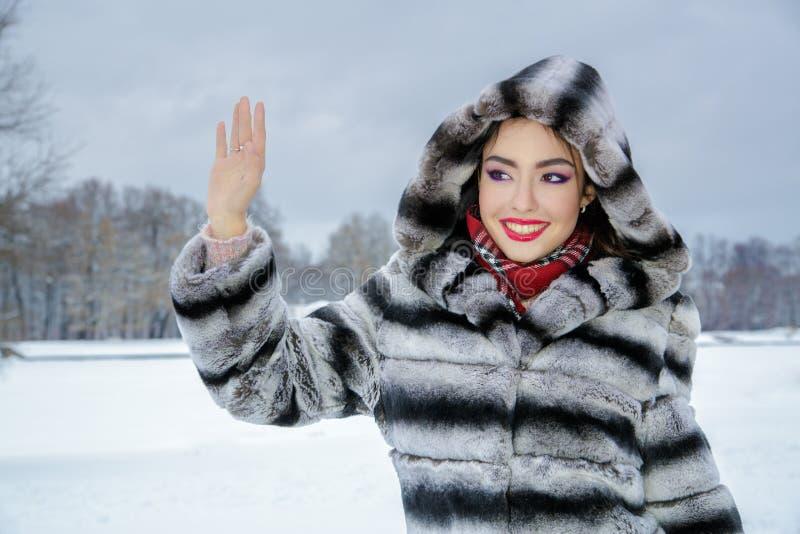 在镶边灰色和黑毛皮大衣挥动有明亮的构成的愉快的快乐的妇女打扮的 免版税库存照片