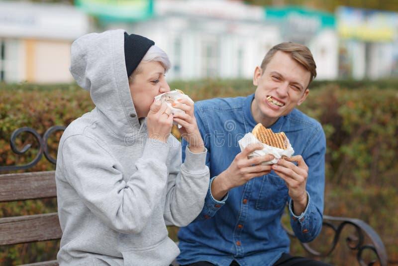 在长凳和微笑的一个公园吃汉堡一对饥饿的年轻夫妇的画象 免版税库存图片