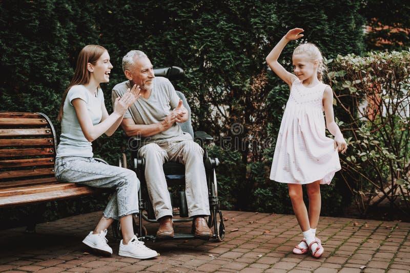 在长凳和轮椅的年迈的和年轻家庭 图库摄影
