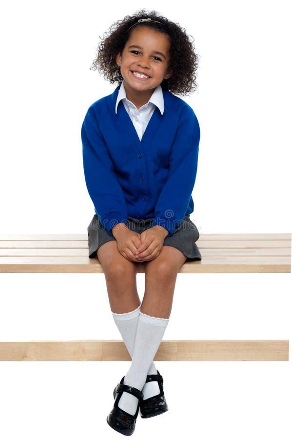 在长凳方便地安装的俏丽的学校女孩 免版税库存图片