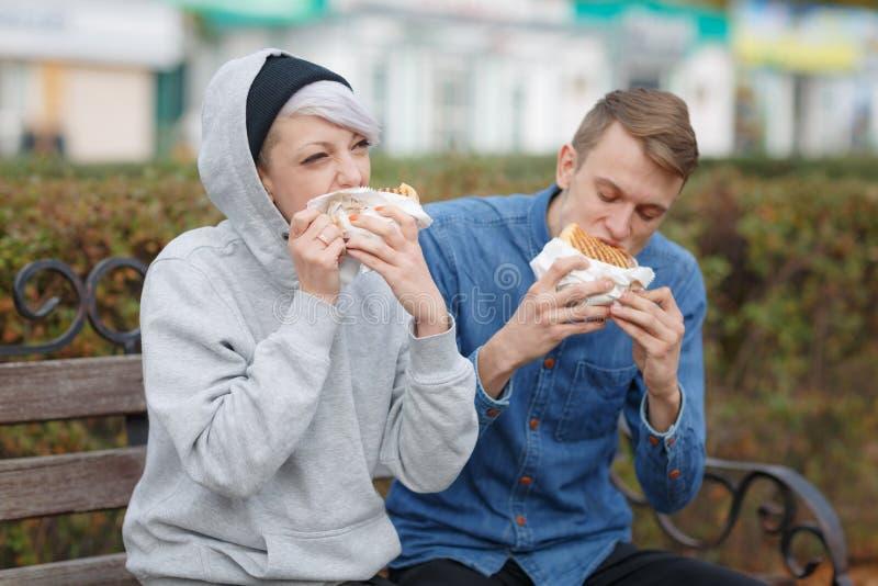 在长凳的公园吃汉堡一对饥饿的年轻夫妇的画象 免版税库存照片