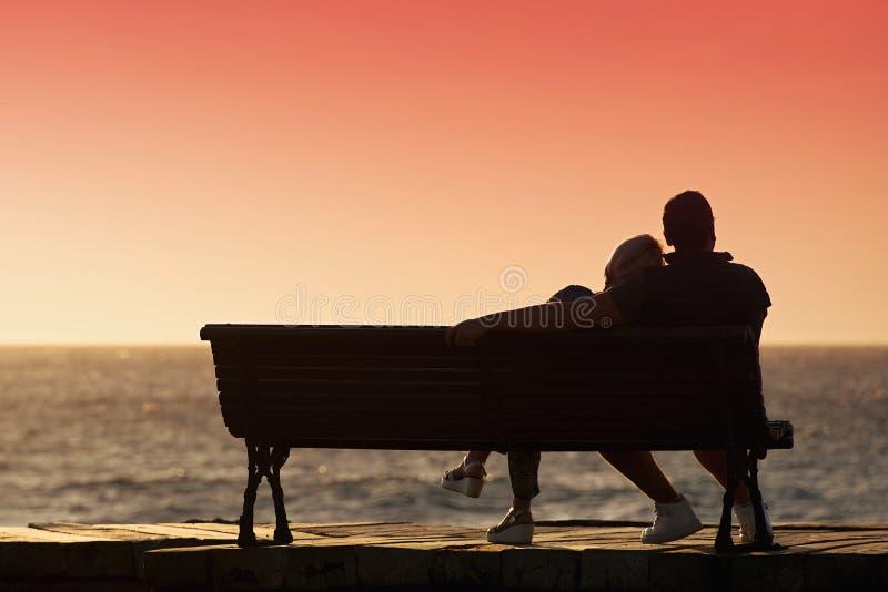在长凳的剪影浪漫夫妇 免版税库存图片