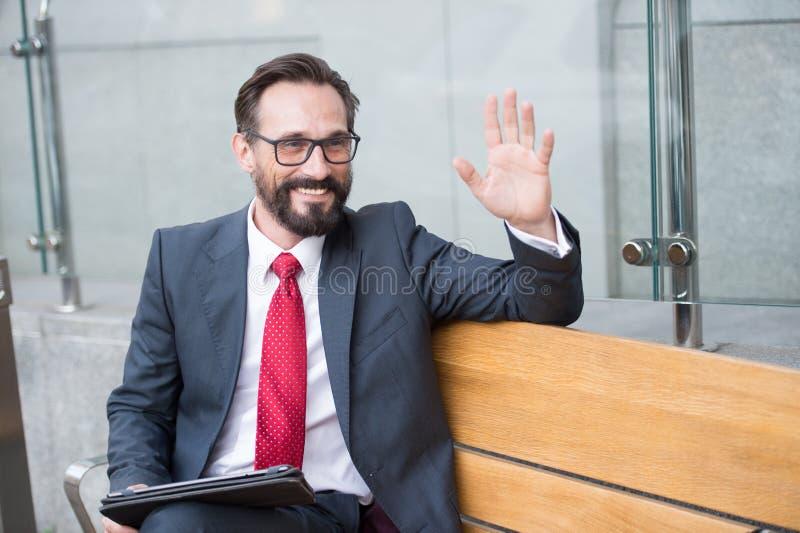 在长凳的商人与片剂在办公室外面的欢迎同事 专业商人在长凳做会议在城市 免版税库存照片