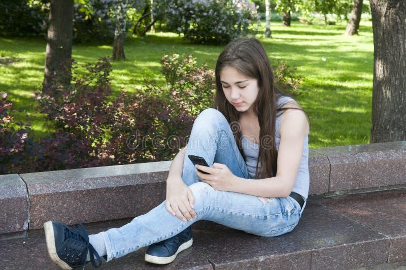 在长凳的年轻有吸引力的女孩用途电话 在公园空白夏天的结构树的云彩 照片 免版税库存图片