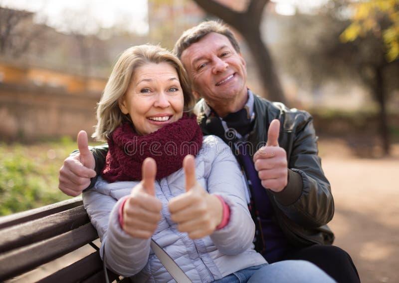 在长凳的成熟家庭夫妇 库存图片