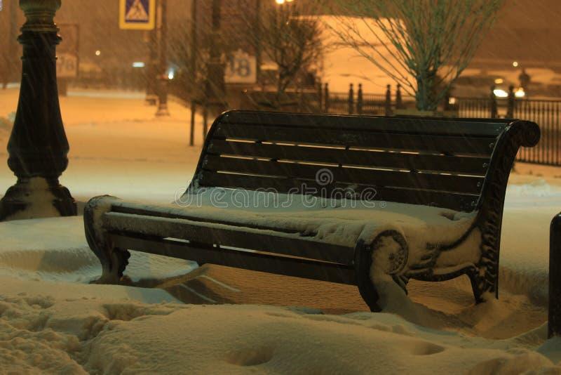 在长凳的晚上飞雪 库存图片