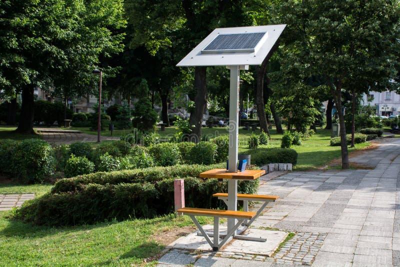 在长凳的流动太阳电池板在充电的公园 库存图片