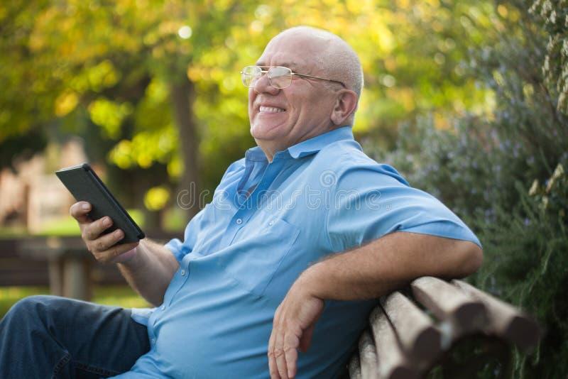 在长凳的老人读书 库存图片