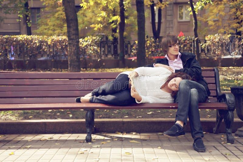 在长凳阅读书的夫妇 库存照片
