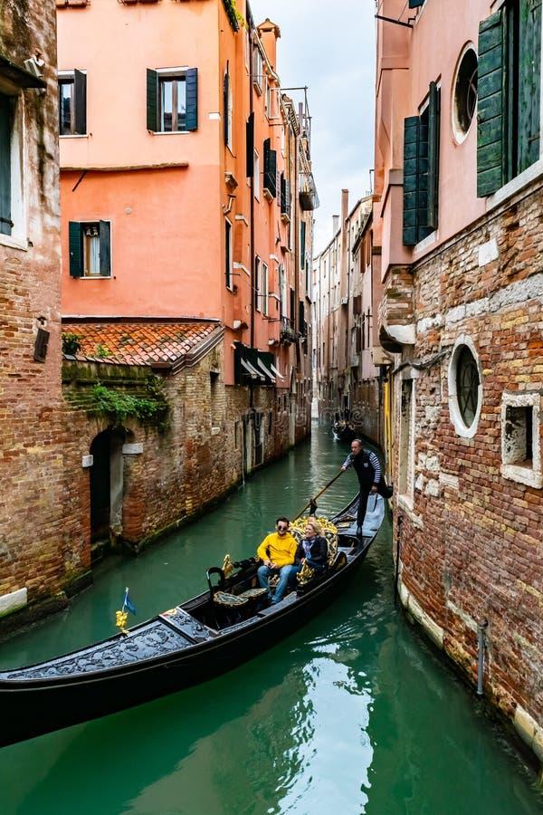 在长平底船的微笑的有吸引力的白种人男人和妇女旅游夫妇骑马 驾驶浪漫游览的平底船的船夫在威尼斯,意大利 免版税库存图片