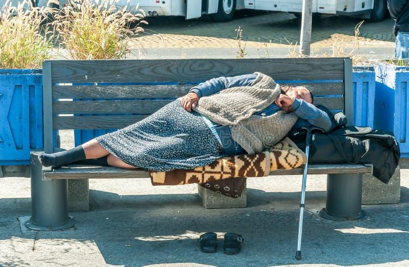在长木凳的无家可归者赤足妇女睡眠在都市街道上在边路的城市 库存图片