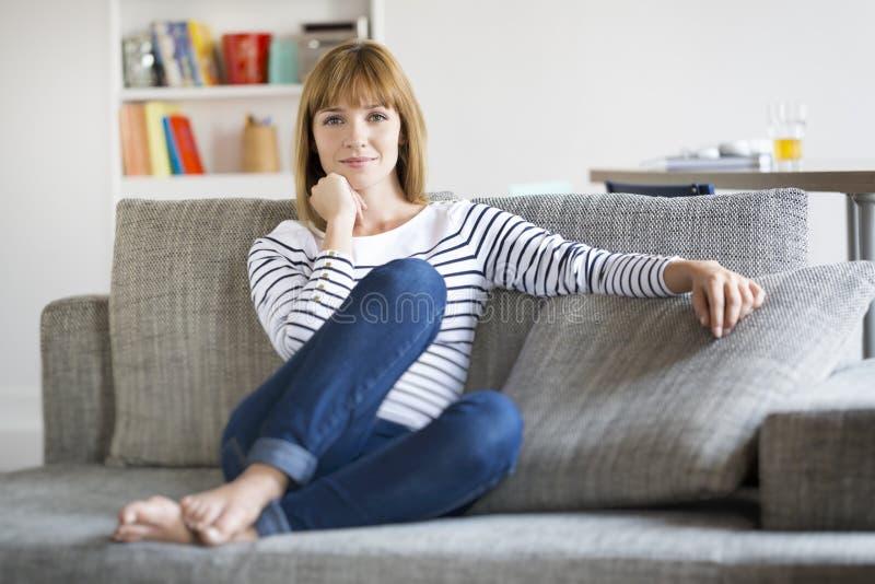 在长沙发安装的自然30岁的妇女在现代家 免版税库存照片