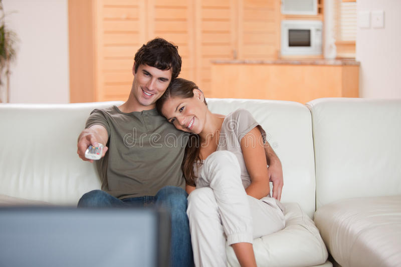 在长沙发注意的电视上的夫妇一起 免版税库存照片
