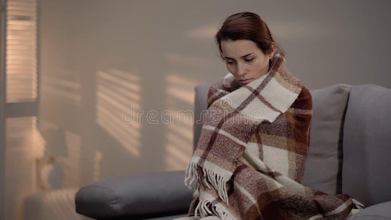 在长沙发的偏僻的沮丧的女性开会,盖用格子花呢披肩,失业 免版税库存照片