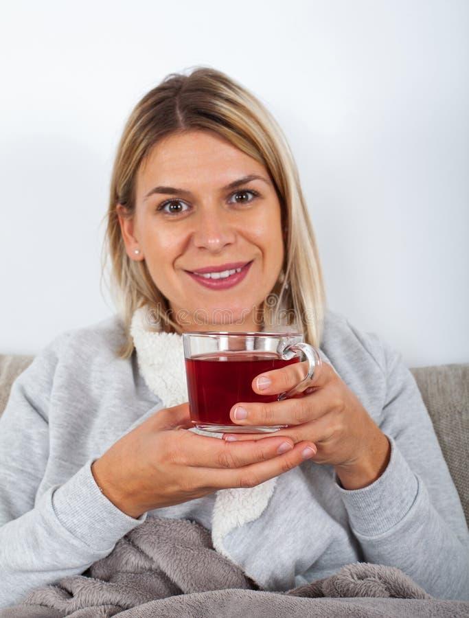 在长沙发的妇女饮用的茶 库存图片