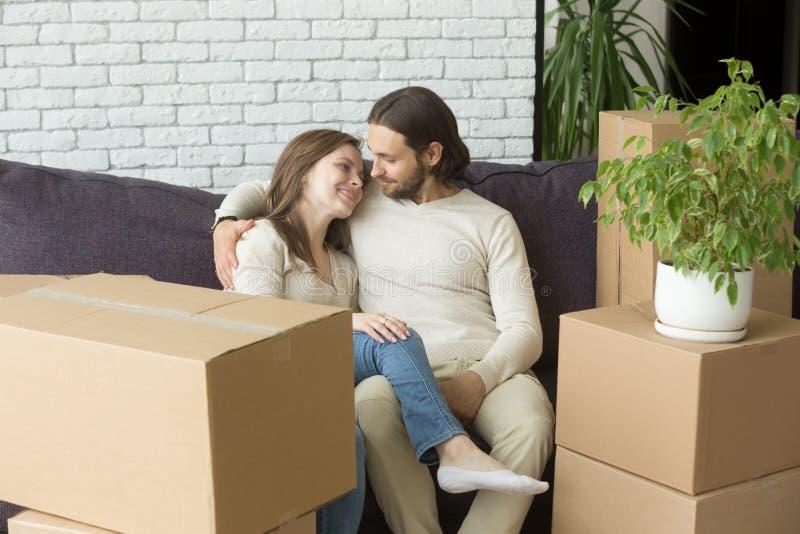 在长沙发的年轻夫妇有箱子的新的家移动了 免版税库存照片