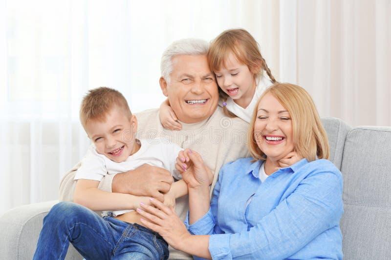 在长沙发的愉快的家庭 免版税库存图片