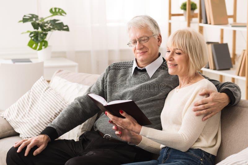 在长沙发的愉快的老夫妇看书在家 图库摄影