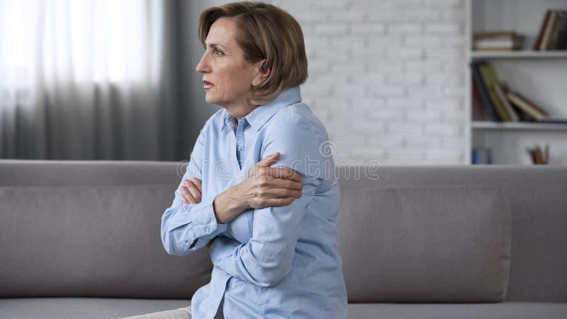 在长沙发的担心的年长女性开会,感觉急切,心理问题 库存图片