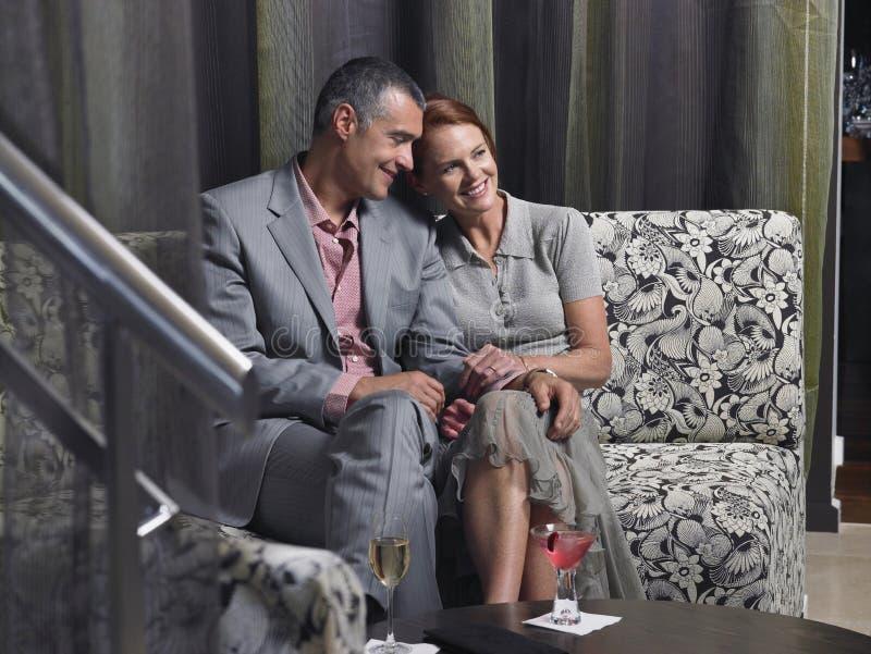 在长沙发的爱恋的夫妇有在旅馆大厅的饮料的 免版税图库摄影