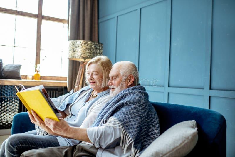 在长沙发的资深夫妇看书在家 免版税库存照片