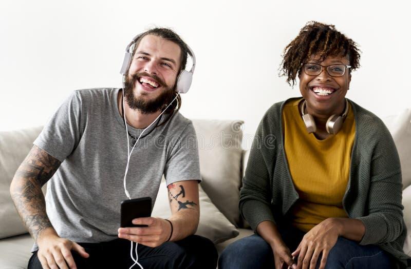在长沙发音乐和友谊概念的人种间夫妇朋友音乐家夫妇 免版税库存照片