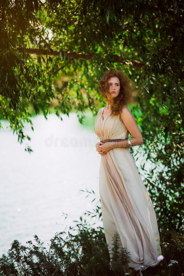 在长米黄礼服摆在的女性模型动态在海滩 挥动的织品 振翼的长的裙子 库存图片
