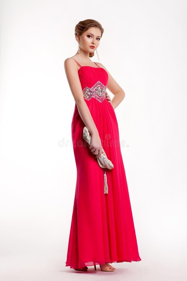 在长红色礼服摆在的时髦时装模特儿 免版税图库摄影
