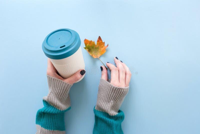 在长袖被编织的毛线衣的手,拿着竹可再用的杯子和秋天叶子,在头顶上在蓝色背景 免版税库存图片
