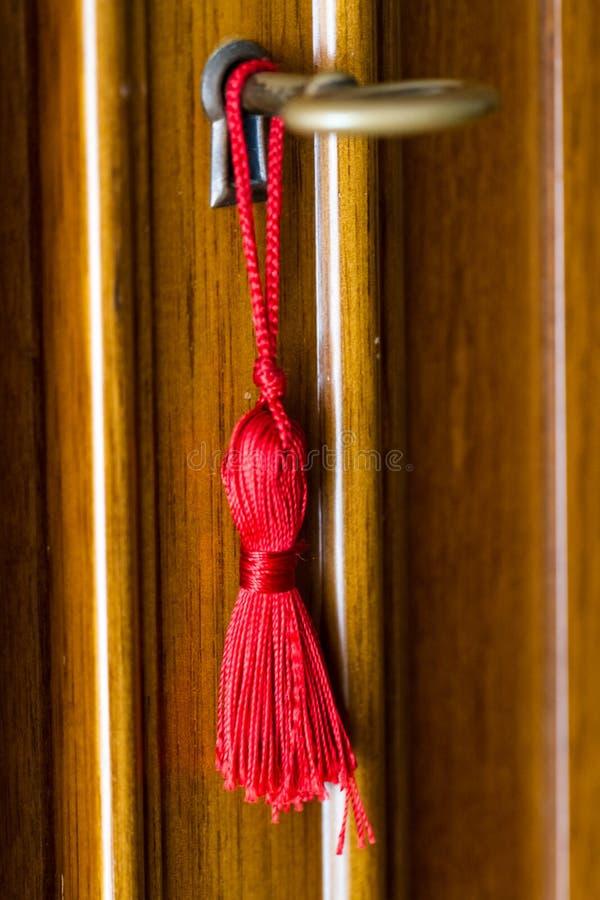 在门匙孔的黄铜钥匙附近被栓的红色缨子 库存图片
