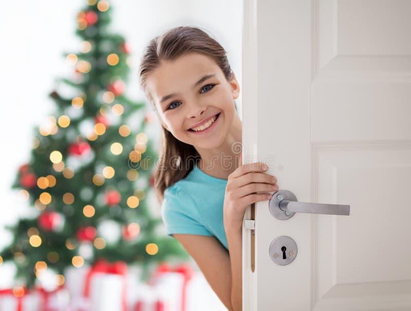 在门后的愉快的微笑的美丽的女孩在家 库存图片