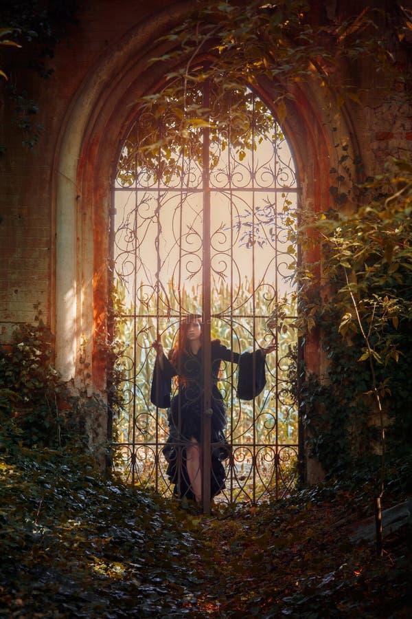 在门后的年轻goth女孩姿势 图库摄影