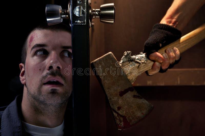 在门的另一边的危险凶手 免版税库存图片