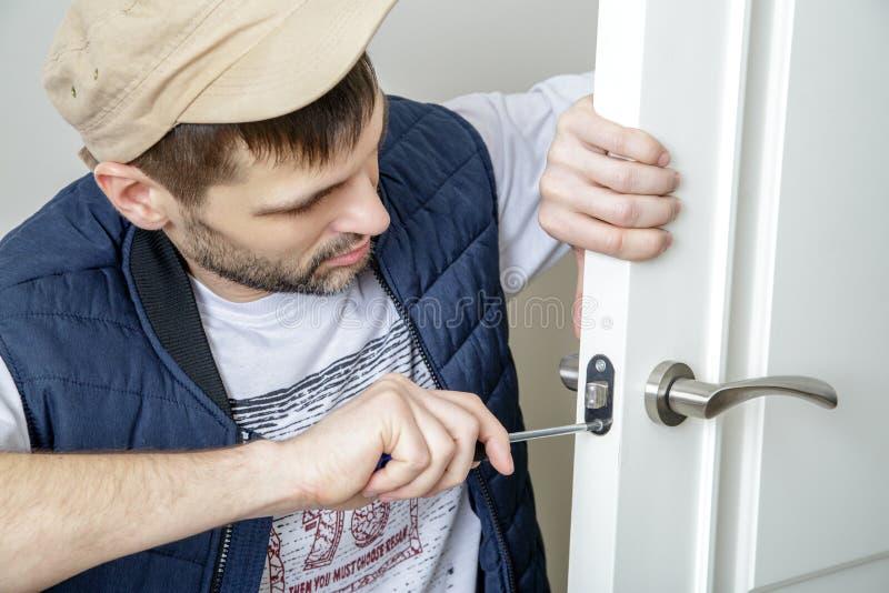 在门的男性木匠定象锁与螺丝刀在家 库存照片