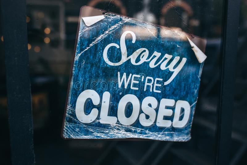 在门的题字:抱歉我们是闭合的 概念性照片或桌在门与工作的信息 公告或 库存图片