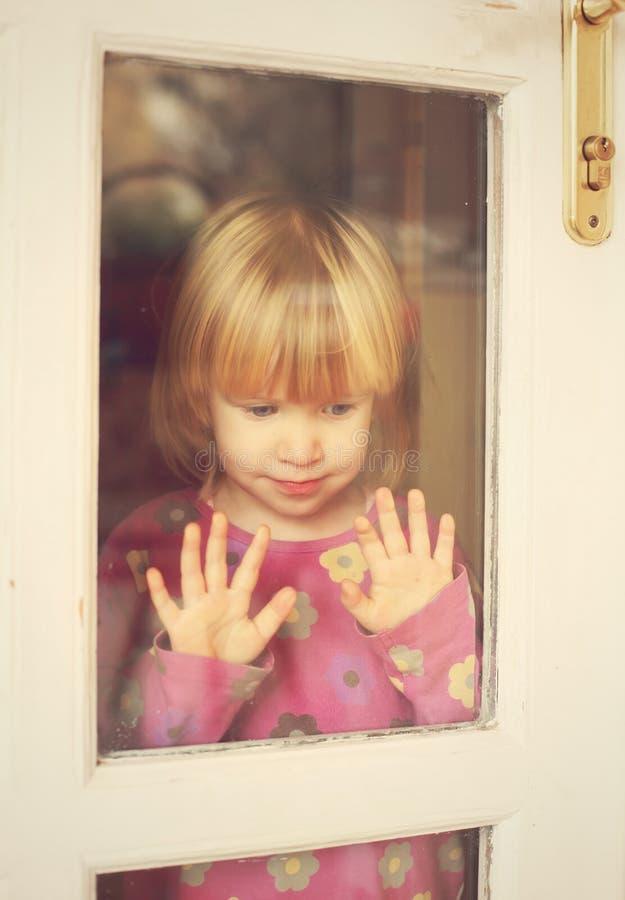 在门窗口的悲哀儿童立场 免版税库存图片