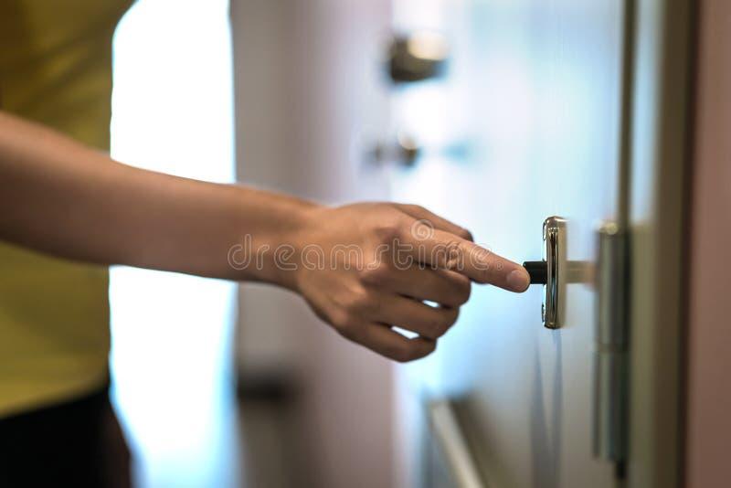 在门铃的手 手指敲响的门铃 免版税库存照片