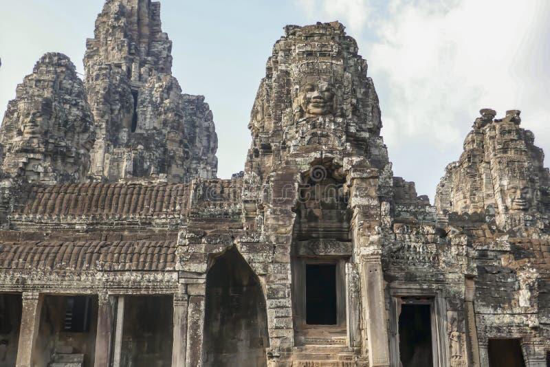 在门面的石头面孔在拜伦寺庙在吴哥汤姆,暹粒市,柬埔寨 免版税库存照片