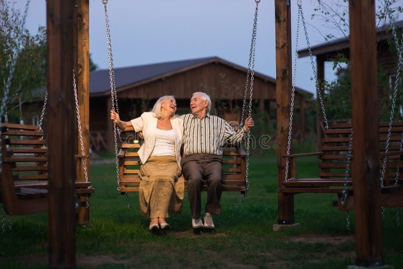 在门廊摇摆的老夫妇 免版税库存照片