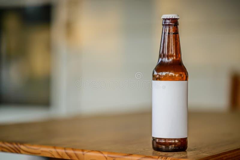 有空白的標簽的一個在門廊/餐桌的啤酒瓶和蓋帽 照片拍攝時間: june圖片