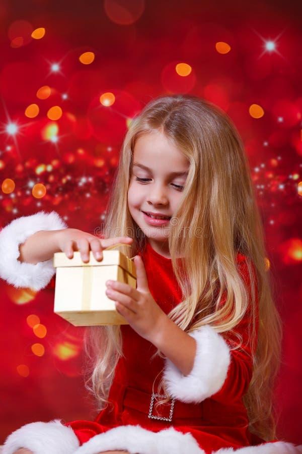 在闪光的背景前的圣诞老人女孩 库存照片