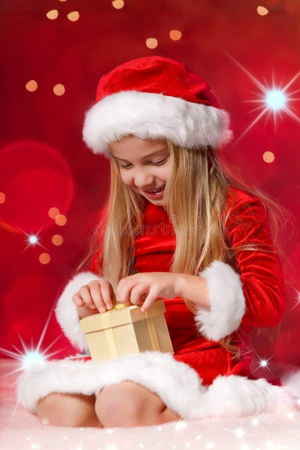 在闪光的背景前的圣诞老人女孩 免版税图库摄影