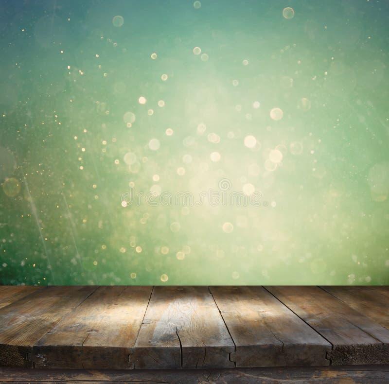 在闪烁银、蓝色和金bokeh前面的土气木桌点燃 免版税库存图片