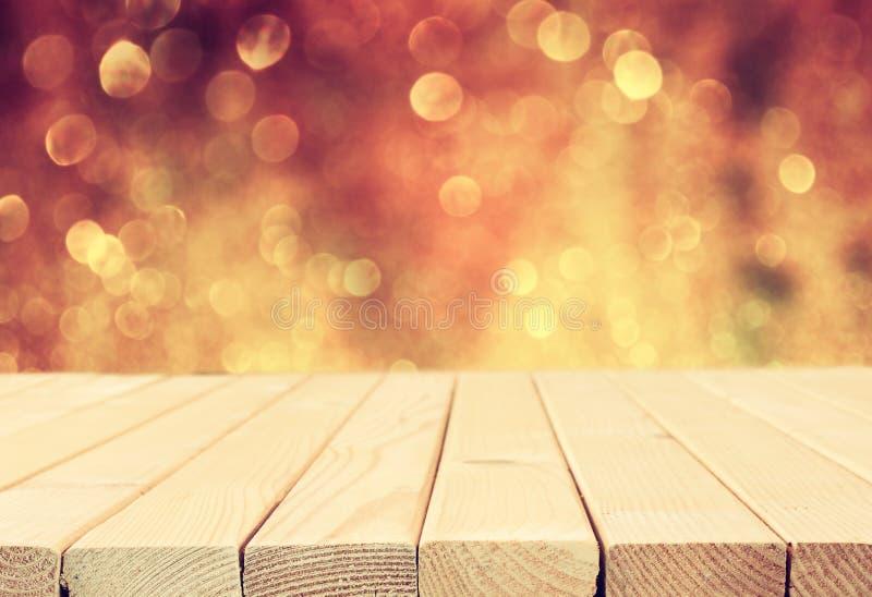 在闪烁银和金明亮的bokeh光前面的土气木桌 免版税库存图片
