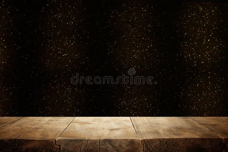 在闪烁黑色和金明亮的bokeh光前面的土气木桌 库存图片