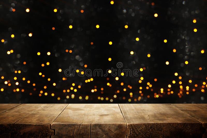 在闪烁黑色和金bokeh光前面的土气木桌 免版税库存图片