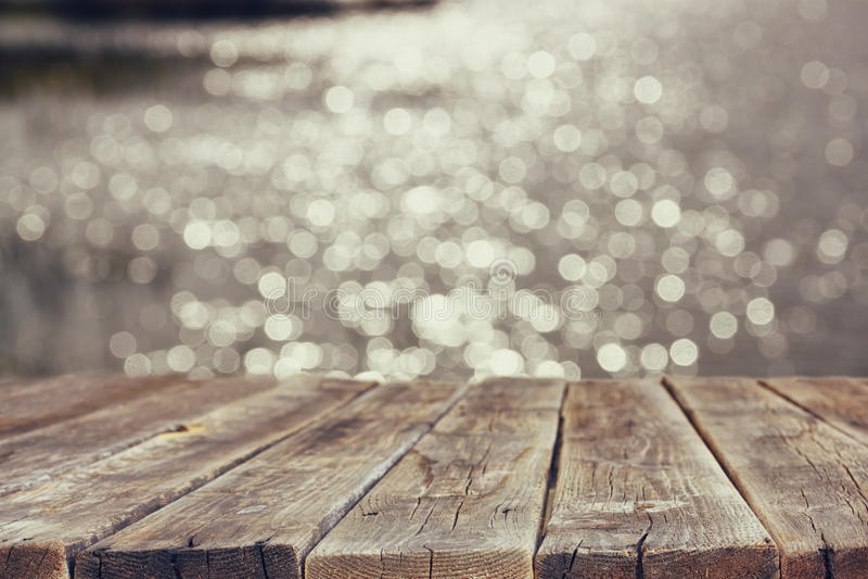 在闪耀的湖水前面夏天风景的木委员会桌  背景被弄脏 图库摄影