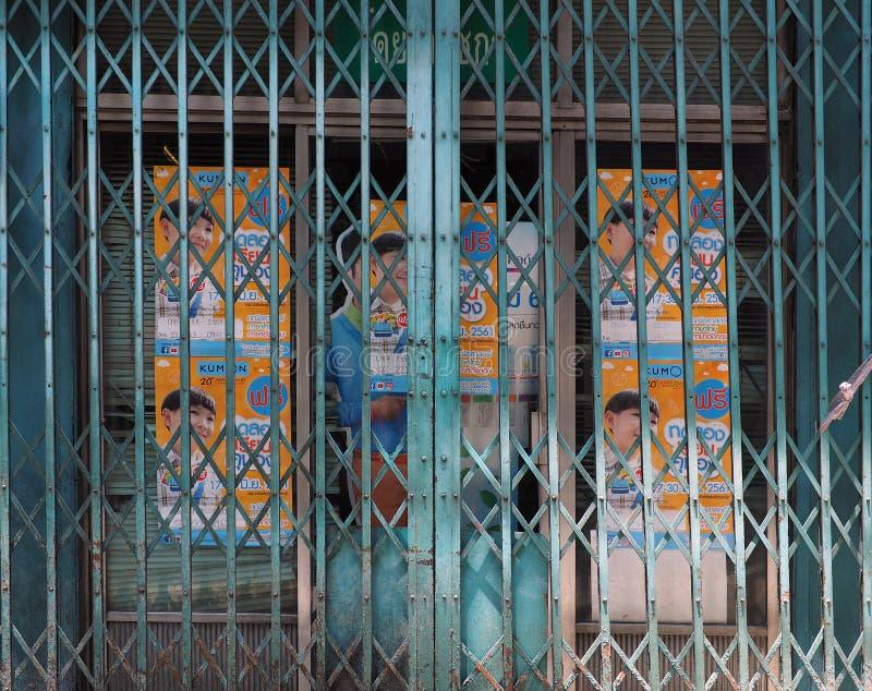 在闭合的可撤回的可折叠金属门后的广告 免版税库存图片