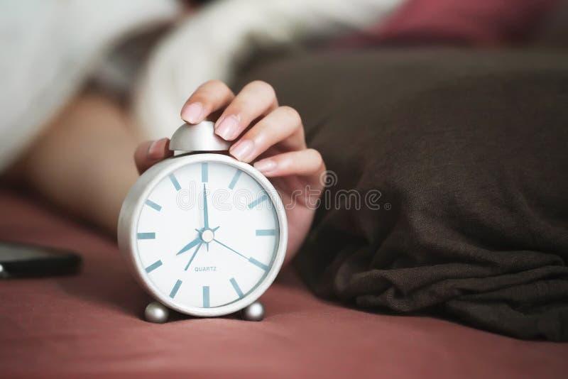 在闹钟上伸手打瞌睡按钮的卧床妇女 免版税库存图片